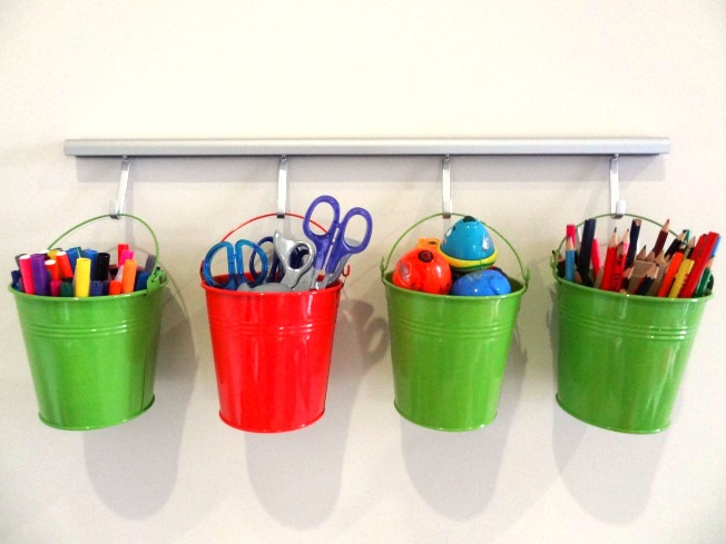 Four dollar store buckets hanging on rail attached to the wall.
