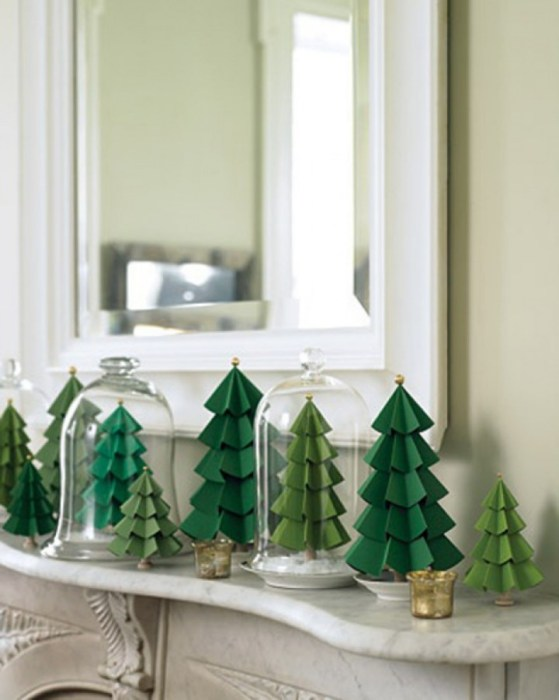 DIY green paper evergreens sat on a mantelpiece.