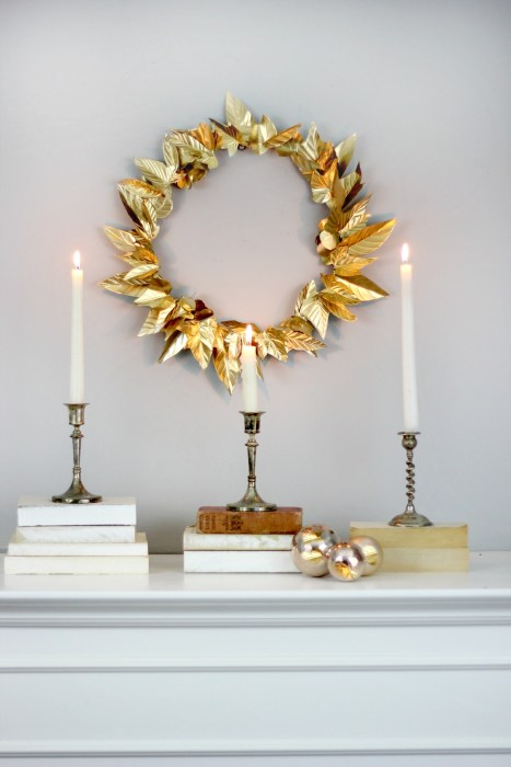 A DIY golden leaf wreath attached to a wall with three lit candles underneath it.