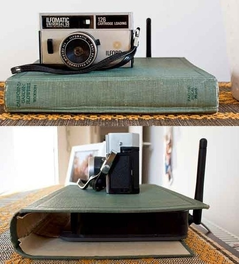 An internet router surrounded and hidden by an old green book cover.