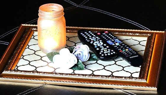 A makeshift storage tray made from a frame holding a candle and remote controls.
