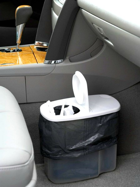 A plastic cereal container on the floor next to the front seat of a car.