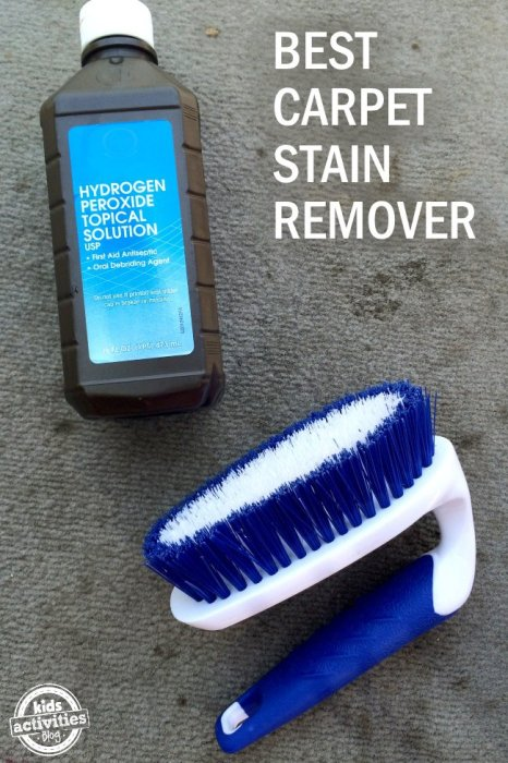 A bottle of homemade car carpet stain remover placed on a dirty carpet