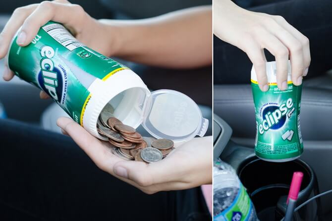 A chewing gum tub filled with coins placed inside a car's cup holder