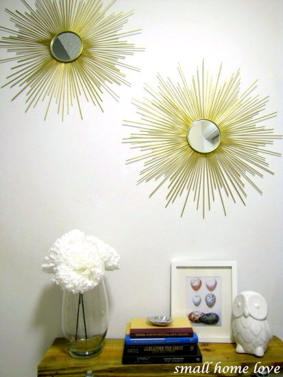 Two homemade, gold-colored starburst mirrors hung to a wall.
