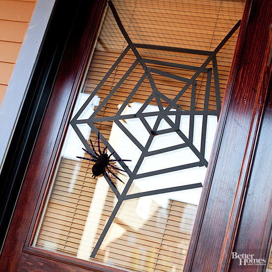 A paper-made spider web with faux spider on a window.