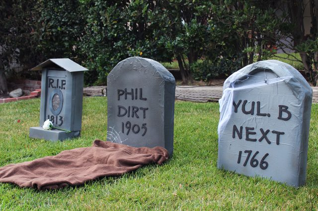 Three cardboard tombstones on a front lawn.