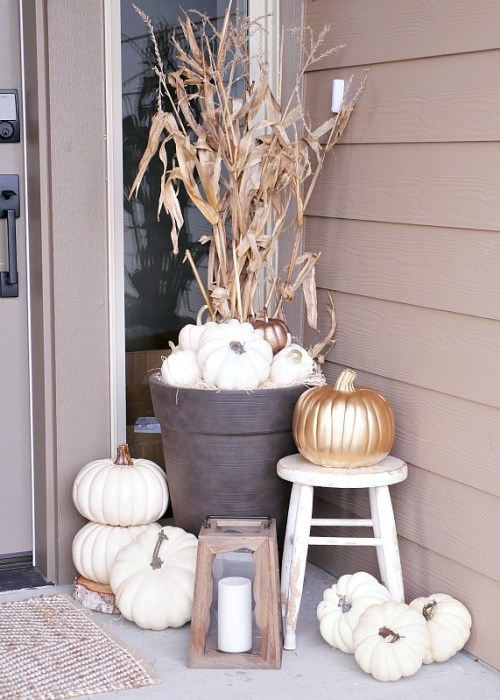 White and metallic gold pumpkins scattered around decoratively in front of a front door.