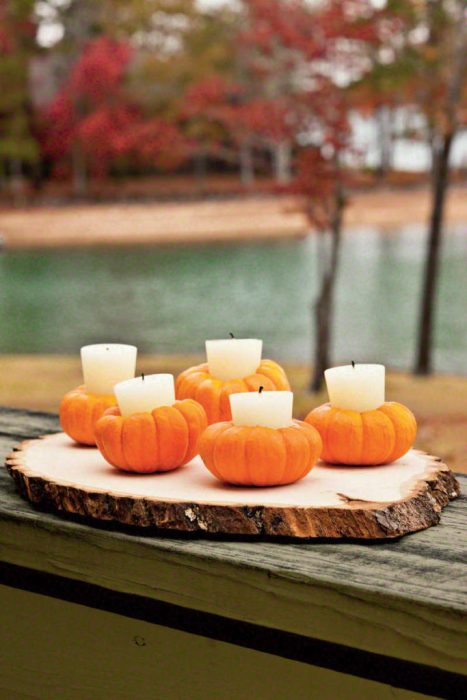 Five small hollowed out pumpkins holding candles.