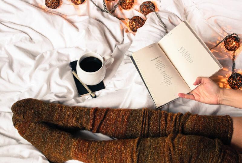 A woman in bed wearing long socks