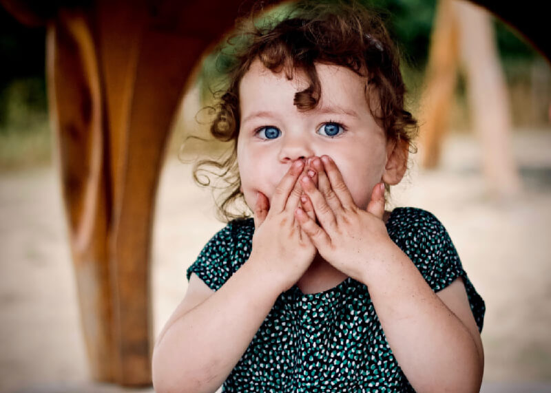 A slightly shocked-looking little girl holding her hands to her mouth to be silent