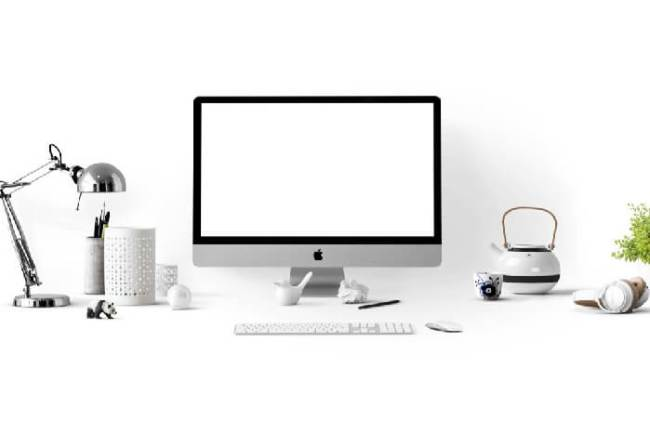 An Apple iMac computer on a white desk.