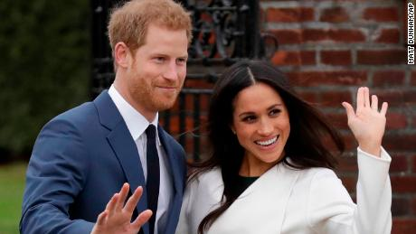 Prince Harry and Meghan Markle wave at the Press while posing for official engagement pictures.