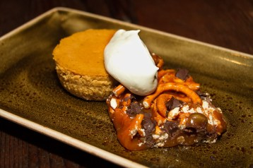 Pumpkin cheesecake served with a salted caramel, pretzel and chocolate brittle as well as bruleed pumpkin