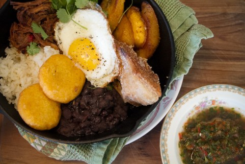 Bandeja Paisa with chicharones, black bean, arroz blanco, fried egg, ahi, ropa vieja, maduros
