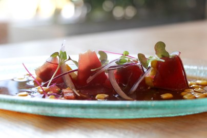 Puerto Caldera Tuna Tiradito made with freshly caught Yellowfin tuna topped with soy sauce, avocado, roasted corn, cilantro, and red onion