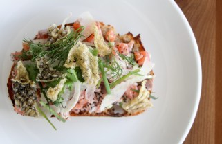 Cured Ocean Trout Smørrebrød served on top of a rye bread mixed with cucumber, dill, poppy seed and topped with fried fish skin