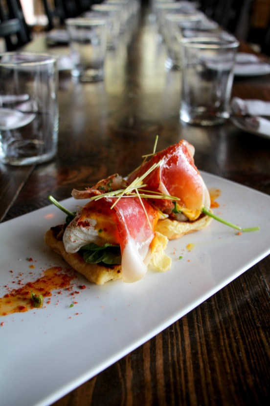 Eggs Benedict served on top of a potato roll, with pork belly, serrano ham and Hollandaise sauce