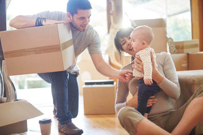A couple with baby with boxes around | Chattanooga Home Inspector | House Hunting Chattanooga