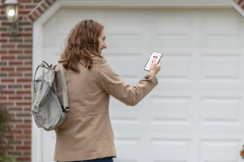 a woman looking at her phone outside the garage | Chattanooga Home Inspector | Connectivity Chattanooga