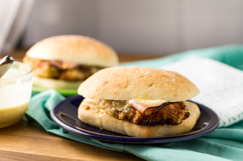 This chicken cordon bleu sandwich is easy and delicious, with crispy chicken topped with ham, Swiss cheese, and honey mustard sauce on a bakery bun! | recipe from Chattavore.com