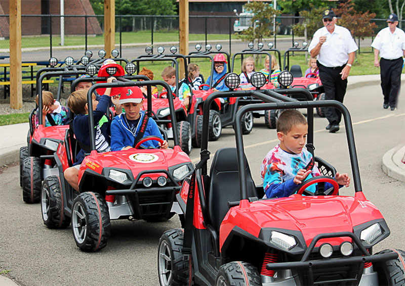 Children driving kid size cars