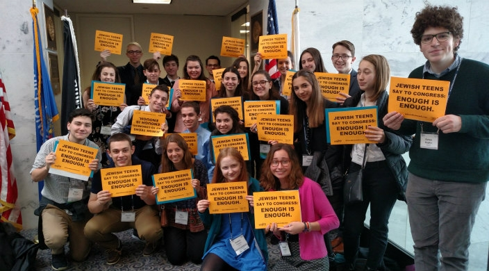 Group of teens holding gun violence prevention signs