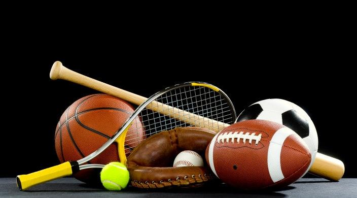 Array of sports equipment, incluing tennis racket and ball, baseball in a glove, baseball bat, football, soccer ball, and basketball