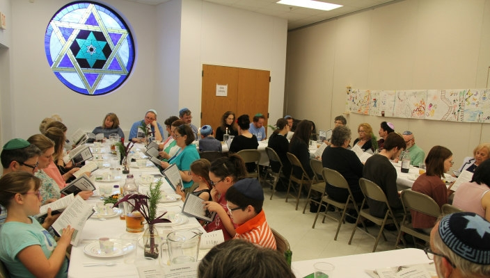 People sitting in a synagogue for the congregations Yom HaShoah ceremony