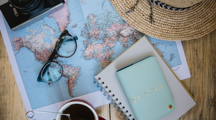 Flatlay of travel items including a map a passport and sunglasses