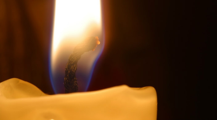 Close-up of flame of single yellow candle
