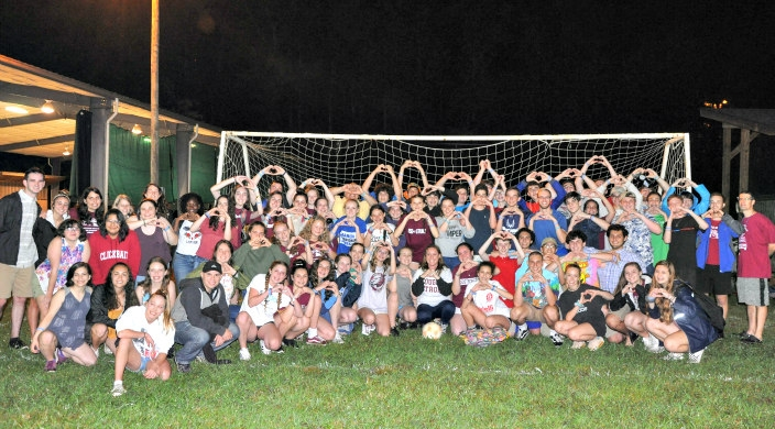 Dozens of campers on a soccer field making a heart shape using their hands