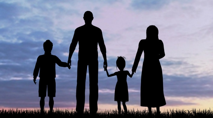 Silhouette of a family standing against sunset
