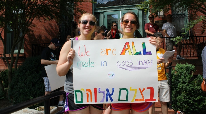Two young women holding a rainbow sign that reads WERE ALL CREATED IN GODS IMAGE