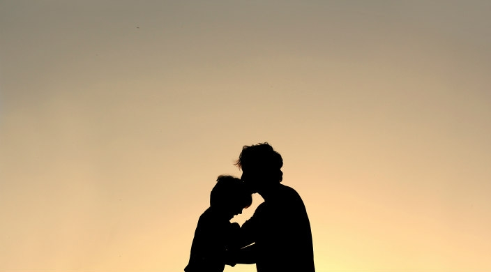 Silhouette of a parent with his or her forehead touching that of a child