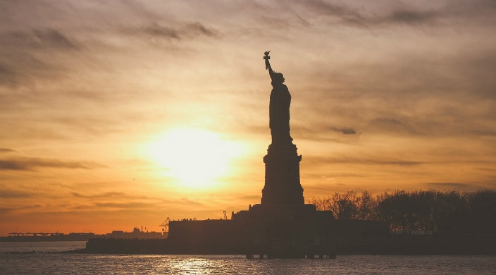 Side view of the Statue of Liberty during an orange sunset