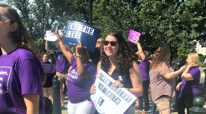 Activist woman protesting outside the Supreme Court in purple shirts carry pro choice signs