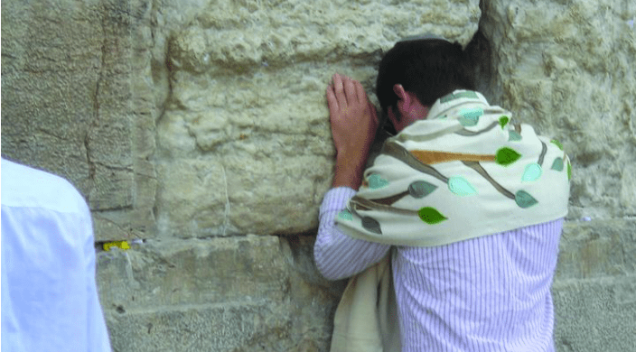 Young person praying intently at the Western Wall in Jerusalem