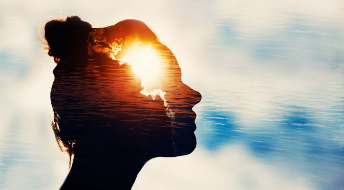 Creative concept image of a woman profile with a bright sunset appearing as though its inside her head