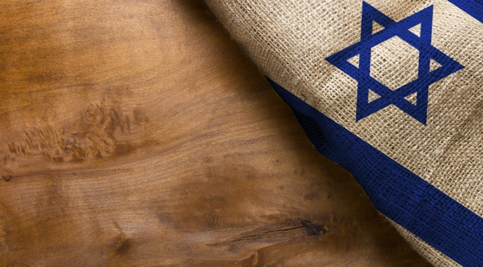 Portion of the Israel flag (Star of David on white background with part of the blue stripes visible) on the righthand part of a wooden surface