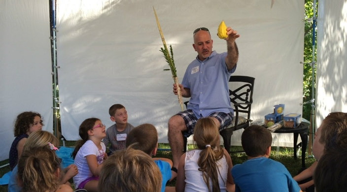 Rabbi Paul Kipnes hold a lulav and an etrog while standing under a sukkah and teaching a group of young children