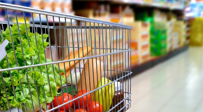 Side view of grocery cart containing produce, bread, and several other items