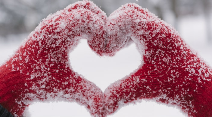Hands in snow-covered red gloves forming a heart