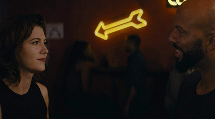 Movie still of a white woman speaking with a black man with a neon arrow shining between as at a bar