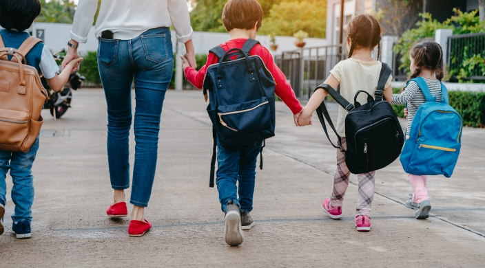 Seen from behind: four young children with backpacks walking hand-in-hand with each other and a mother or caregiver