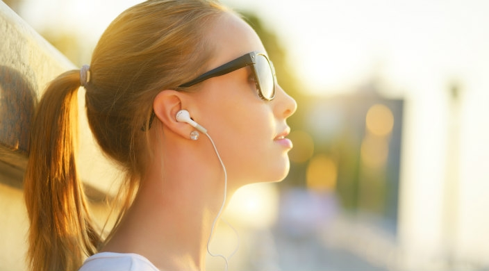 Young woman in profile with a ponytail and sunglasses wearing earbuds