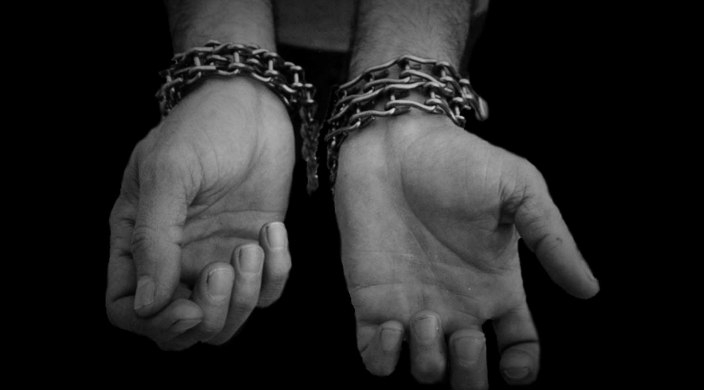 Black and white image of a persons hands bound with chains