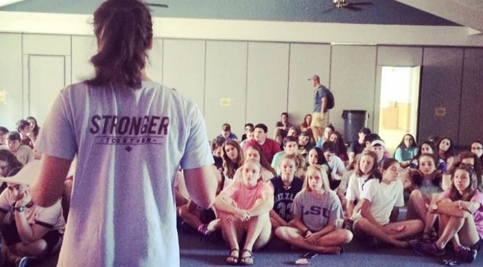 Teen girl facing away from the camera in a shirt that reads STRONGER in front of a seated audience of other teens