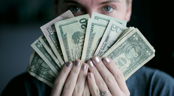 Closeup of a person holding a fanned out handful of money