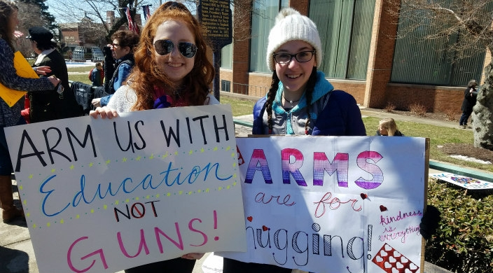 Two high school girls holding gun violence prevention signs at a march